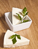 Triangle pieces of cheese. With parsley in white bowl on wooden board Stock Images