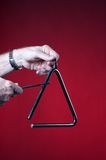 Triangle Played Isolated on Red. A musical triangle being played by hands isolated against a red background in the vertical format with copy space Royalty Free Stock Photo