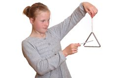 Triangle player. A young girl plays with a triangle isolated on white background Stock Photo