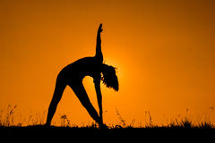 Triangle pose yoga with young woman silhouetted. Stock Photos