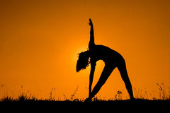 Triangle pose yoga with young woman silhouetted. Royalty Free Stock Photo