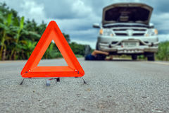 Triangle Red emergency stop sign, with repair broken, damaged cars parked on the street Royalty Free Stock Images