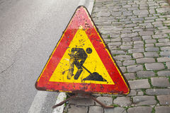 Triangle red and yellow roadsign on urban roadside. Men at work, road under construction royalty free stock images