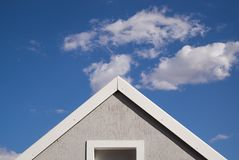 Triangle Roof of a House. Triangle shaped house and roof against blue sky and clouds background Stock Images