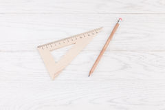 Triangle ruler and pencil on wooden background Royalty Free Stock Photos