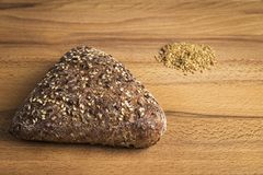 Integral bread in the form of a triangle with linseed, oats and sesame seeds. Triangle-shaped wholemeal bread with linseed, oats and sesame seeds next to some stock photos