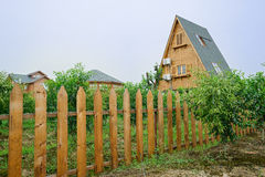 Triangle-shapend wooden cabin in fenced orchard Royalty Free Stock Photography