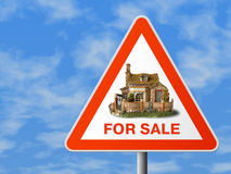 Triangle sign with house (for sale). Sky background royalty free stock photo