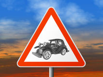 Triangle sign with vintage car. Sunset on background Stock Image