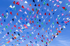 Triangle String Pennant. Colorful Triangle flag pennants blowing in the wind against a blue sky Royalty Free Stock Photo