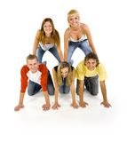 Triangle from teenagers. Small group of happy teenagers. Smiling and looking at camera. Creating triangle from their bodies. White background, front view Royalty Free Stock Image