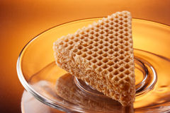 Triangle wafer cookie on glass plate Royalty Free Stock Photography