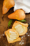 Triangle wraps of puff pastry with pear Stock Images
