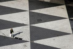 Triangled Square. Square with triangles, lonely pedestrian stock photo