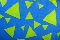 Triangles matérielles vertes sur le tissu bleu lumineux Photographie stock