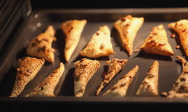 Triangles of puff pastry inside oven Royalty Free Stock Images