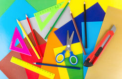 Triangles, ruler, scissors, pencils and cutter on colored paper Stock Photo