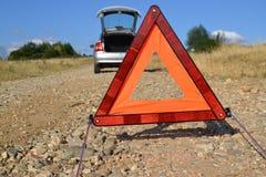 Triangolo d'avvertimento laterale della strada dietro un'automobile Fotografie Stock