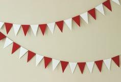 Triangulära pappers- handgjorda girlander av vitt och rött på en ljus vägg arkivfoton