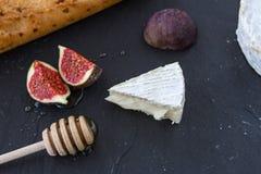 Triangulärt aptitretande stycke av camembertost, stycken av fikonträd i honung och en träsked för honung och bagett på en grafit  royaltyfri bild