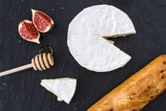 Triangulärt aptitretande stycke av camembertost, stycken av fikonträd i honung och en träsked för honung och bagett på en grafit  arkivfoto