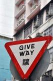 Triangulärt ge brädet för vägtrafikvarning och en fågel Royaltyfri Foto