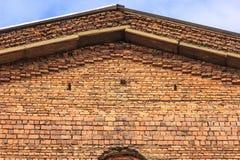 Triangulärt tak av en gammal byggnad av orange tegelstenar mot en blå himmel royaltyfria foton