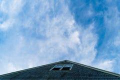 Triangulärt tak som pekar in mot en härlig blått, litet molnig himmel, kvarterö, RI arkivbild
