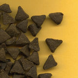Triangular cat biscuits. Scattered brown triangular car biscuits on yellow background stock photography