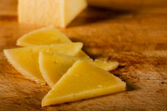 Triangular Cheese on Wooden Board Stock Photography