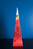 Triangular colored candle. Big candle posed on a blue shelf Stock Photography