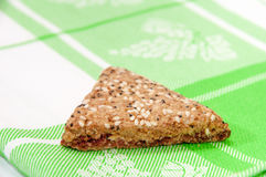 The triangular cookies with cherries on green kitchen tablecloth Royalty Free Stock Images