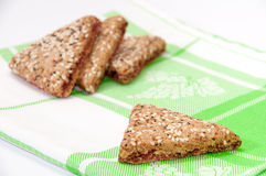 The triangular cookies with cherries on green kitchen tablecloth Stock Photography