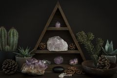 Triangular Crystal Shelf with Plants Foliage Gems and Jewellery on a Wooden Surface royalty free stock image