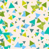 Triangular geometric seamless pattern with colorful green, blue random triangles on pastel beige background. Stock Photography