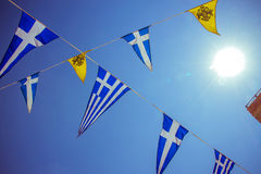 Triangular Greek sea flags on blue sky, sun Royalty Free Stock Images