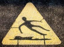 Triangular Hazard Symbol of Man Slipping on Water and Falling. Yellow and black triangle hazard or warning symbol showing man slipping on water signifying stock image