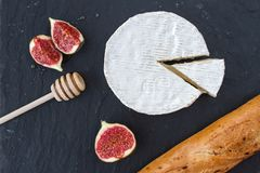 Triangular piece of camembert cheese and a formed cheese, figs in honey and a wooden spoon for honey and browned baguette on a gra. Triangular appetizing piece Stock Photos