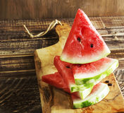 Triangular pieces of a water melon on a kitchen board Stock Photos