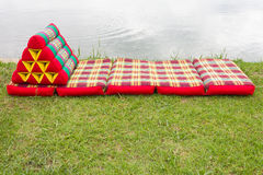 Triangular pillows and mattresses on the grass. Royalty Free Stock Image
