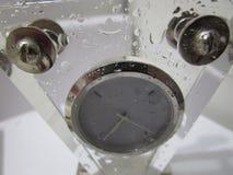 Triangular prism desk clock wet with water droplets. Transparent triangular prism shape desk clock wet with water droplets stock photos