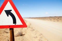 Triangular road sign indicating left turn Royalty Free Stock Image