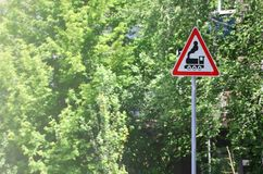 Triangular road sign with a picture of a black locomotive on a white background in a red frame. Warning sign for the presence of. A railway crossing the motor Stock Photography