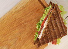 Triangular sandwich on a wooden Board Stock Photos