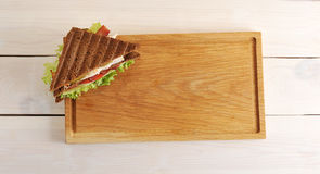 Triangular sandwich on a wooden Board Stock Photography