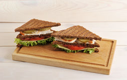 Triangular sandwich on a wooden Board Royalty Free Stock Image
