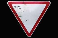 Triangular scratched red border road sign `Yield` isolated on bl. Ack royalty free stock images