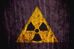 Radioactive ionizing radiation danger symbol painted on a massive concrete wall. Triangular yellow and black radioactive ionizing radiation danger symbol painted Royalty Free Stock Photography
