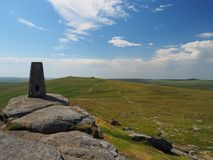Triangulation pillar on Yes Tor looking to High Willhays with white clouds in a blue sky, Dartmoor Stock Photo