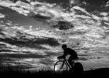 Triathlet, das in Sonnenaufgang einen Kreislauf durchmacht Lizenzfreie Stockfotos